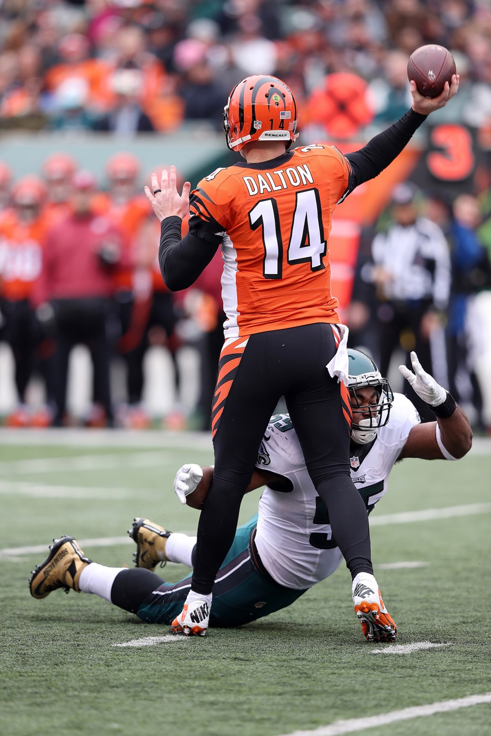 The Bengals Andy Dalton gets hit low, drawing a penalty. Low hits on quarterback will be strictly enforced by NFL game officials in 2017. (Paul Spinelli via AP)