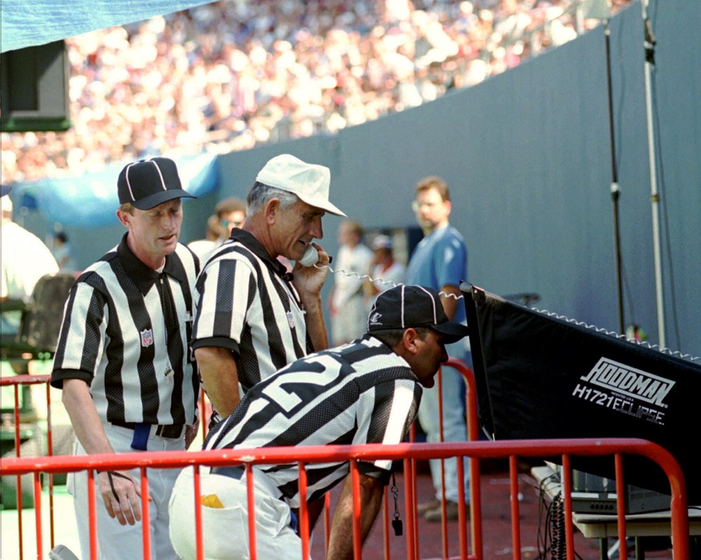 Referee Bob McElwee reviews a play with an on-field monitor during the 1996 preseason testing of the new system. (AP Photo/Bill Kostroun)