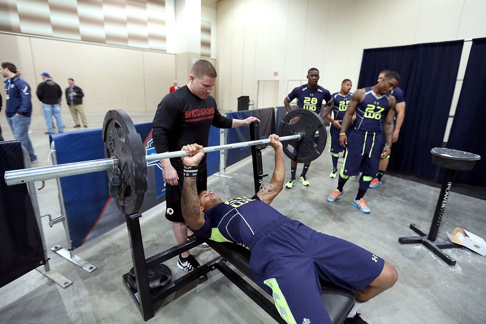 Scouts watch as an NFL prospect completes the bench press. (AP)