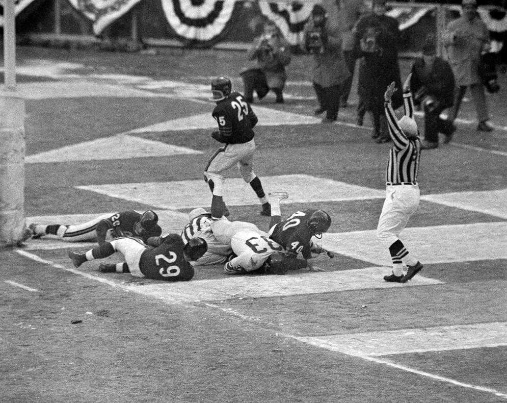 Umpire Sam Wilson signals for a touchdown in the 1956 NFL championship game between the Chicago Bears and the New York Giants. (AP Photo/Harry Harris)