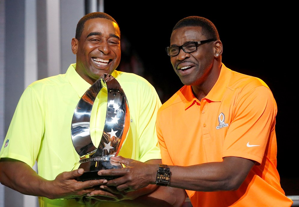 Michael Irvin, right, and Cris Carter, left, NFL Hall of Fame members and Pro Bowl Alumni captains, laugh during the Pro Bowl Kickoff news conference Tuesday, Jan. 20, 2015, in Phoenix. (AP Photo/Ross D. Franklin)