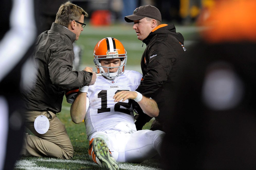 Trainers tend to Cleveland Browns quarterback Colt McCoy (12) after he was hit by Pittsburgh Steelers outside linebacker James Harrison in the fourth quarter of an NFL football game in Pittsburgh on Dec. 8, 2011. (AP Photo/Don Wright)
